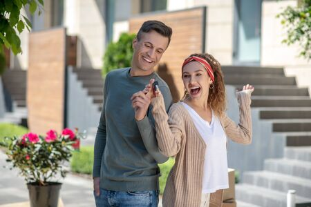 Happiness. Happy young couple feeling amazing after getting the key from their new house