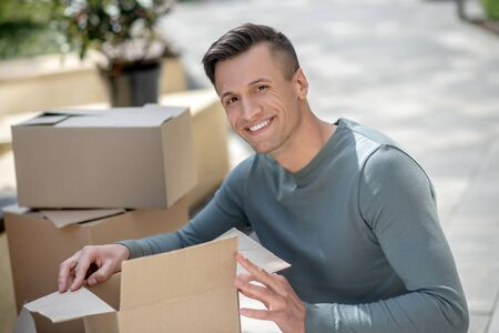 Packing. Smiling handsome man sitting next to the cardboards
