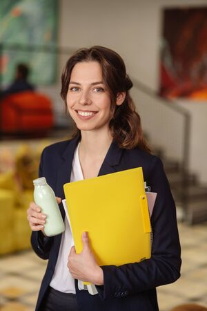 Office employee. Successful business girl standing with a small bottle of drink and a yellow folder, smiling joyful