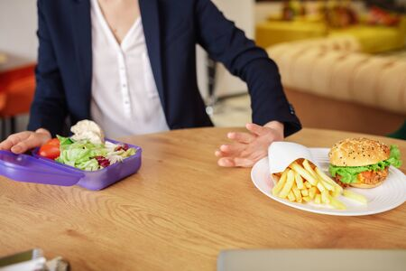 Decision-making. Female hand gesturing refusing fast food another holding purple lunchbox with chopped vegetables
