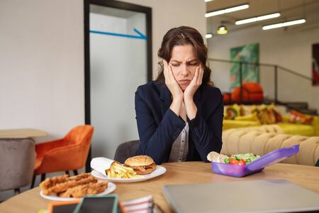 Discontent. Young adult girl with grimace of discontent looking at fast food on plates, on the other side an open lunchbox with vegetables