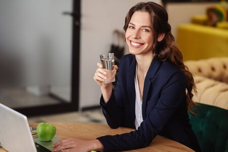 Success, mood. Young adult successful girl with a glass of water in hand, sitting in front of a laptop in the office, smiling
