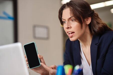Online chat. Emotional serious girl with open mouth showing a smartphone in front of a laptop screen, frowning.