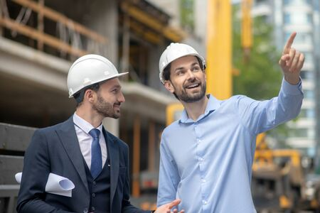 Building site. Foreman pointing his hand, showing something to building supervisor Banque d'images