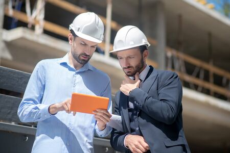 Building site. Foreman showing something on his tablet to building supervisor, who is touching his chin Banco de Imagens