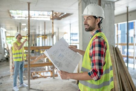 Building site. Building worker in yellow vest holding blueprint, his colleague standing in the background, checking construction Foto de archivo