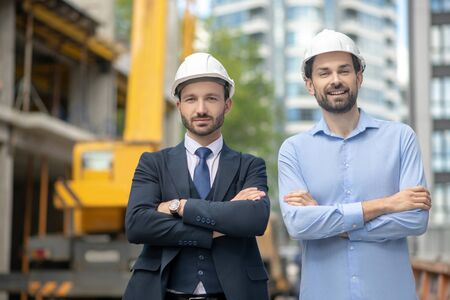 Building site. Foreman and building supervisor standing with folded arms on the building site Stockfoto