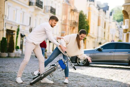 Lost balance. Man in white sweater and jeans picking up a fallen bicycle with a young injured woman