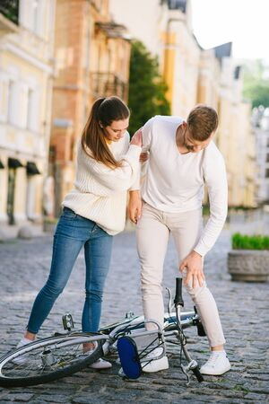 Hurts to fall. Bearded young man with knee injury and woman standing over bicycle with head down