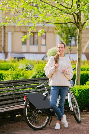 Leisure. Happy smiling girl in jeans and sweater with bottle of water in her hands standing near the bicycle in the park