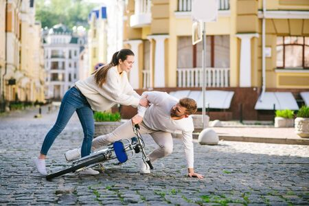 Giving help. Young pretty woman holding out her hand to an unfortunate man who fell with a bicycle, helping