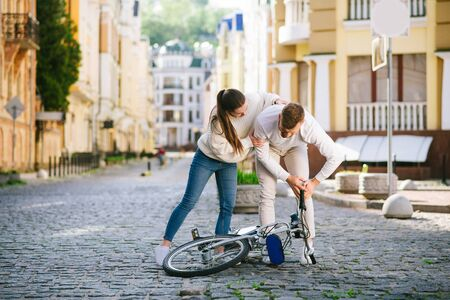 Fall on road. Young adult man and woman in casual light clothes bent over a fallen bicycle on the road. Stock Photo