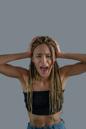 Inner pain. Devastated young African American holding her head in hands, screaming