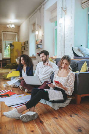 Involved in work. Girl with smartphone, guy with laptop and girlfriend with papers sitting on floor in comfortable modern studio working concentrated Foto de archivo