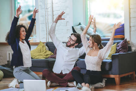 Success. Three smiling young students friends sitting on floor in room with their hands upstairs with open mouths rejoicing in overall success.