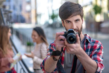 Photography, lens. Serious attractive dark-haired guy with brown eyes holding camera looking straight with concentration, two girls at distance Banco de Imagens