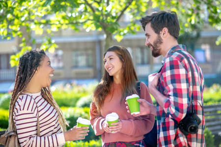 Delight, communication. Enthusiastic mulatto girl with dreadlocks with open mouth and opposite girlfriend and boyfriend all standing with coffee