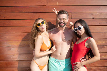 Having fun. Young handsome man standing and hugging two beautiful women in swimming suits 版權商用圖片