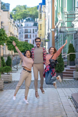 Freedom. Bearded guy in sun-protection glasses and two girls bouncing up together, raising his hands, opening his mouth, enthusiastic on street.