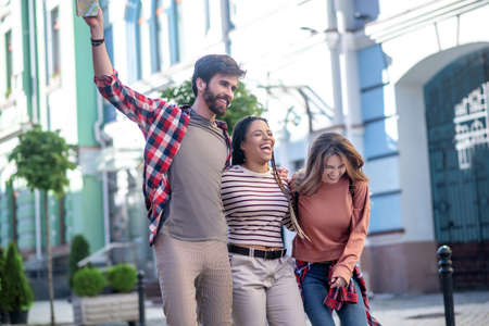 Very funny. Three cheerful young friends with a map traveling around the city, having fun, hugging, laughing.