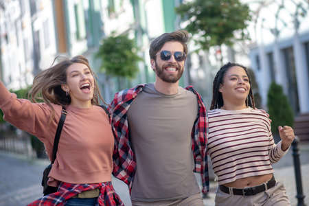 Happy moment. Guy in plaid shirt with sun glasses and two pretty long-haired girls walking enthusiastic laughing with open mouths