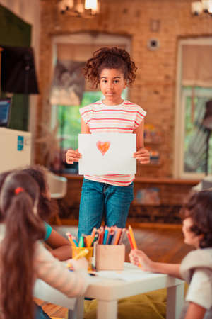 Cute pictue. A girl showing a picture of the heart she drew
