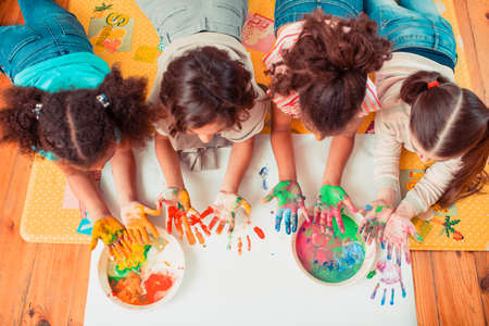 Funny art classes. Children painting with their hands during the art class