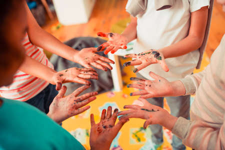 Dirty fingers. A group of children having their hands stained with watercolors