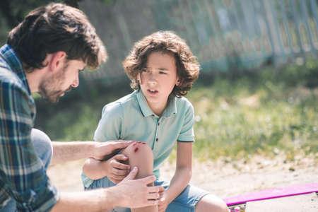 Injury. Man in a checkered shirt examining his sons injured knee
