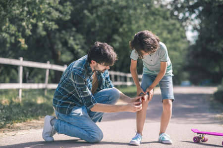 Injured knee. Dark-haired boy touvhing his imjured knee, his gather helping him Banque d'images
