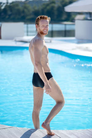 Open pool. Tall sporty smiling red-haired man looking back near the pool, leg bent at the knee
