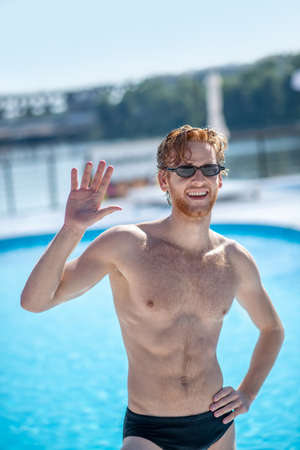 Glad to see. Smiling man with open mouth in sunglasses and swimming suit raised his hand welcomingly near pool