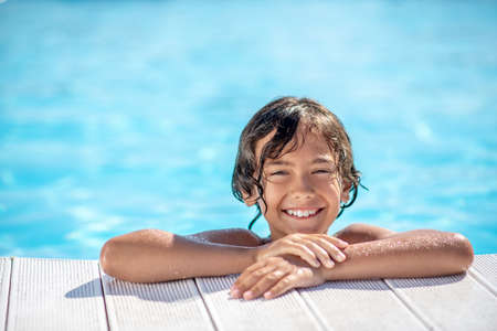 Enjoyment. Satisfied smiling face of tanned boy peeking out of the outdoor swimming pool