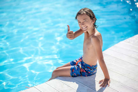 All perfectly. Happy smiling boy in shorts sitting by pool showing with hand gesture everything is ok Stock Photo