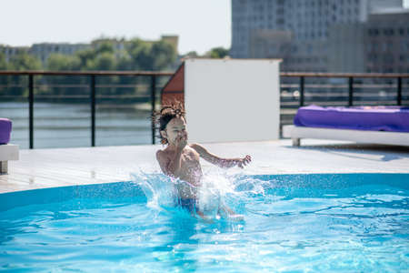 Immersion in water. Energetic boy covering his nose with his hand diving under water in an outdoor pool 版權商用圖片