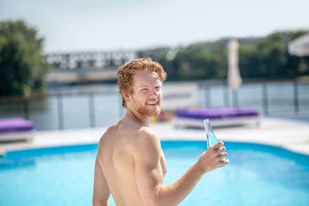 Near pool, heat. Looking back joyful man with bottle of drinking water standing near outdoor swimming pool
