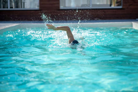 Swimmer, skill. Swimmer swimming in the pool head underwater, hand high above the water