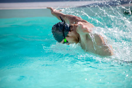 Swimming style. Swimmer in water while throwing his hands out of water head above water and lot of splashes 版權商用圖片