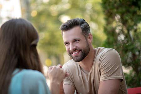 Loving relationship. Smiling bearded male sitting opposite female in blue dress, holding her hand