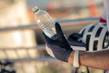 Freedom. Open bottle of water in the male hand of a cyclist in sports glove, outdoors