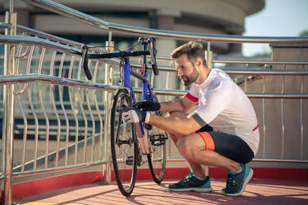 Bicycle inspection. Young adult man in sportswear and gloves crouching downstairs and inspecting bicycle, on the street Archivio Fotografico