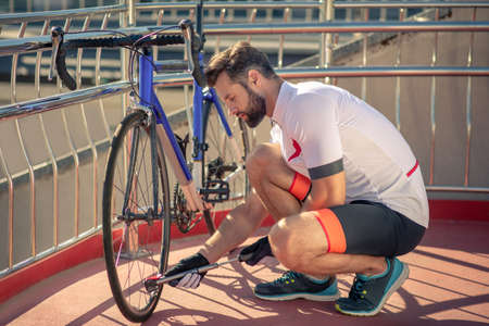 Bicycle wheel, pump. Young bearded man with pump crouching near bicycle wheel easily coping with problem