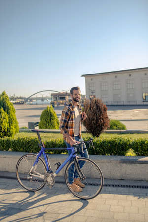 Great day. Energetically walking bearded man in casual comfortable clothes with bike on sunny day outdoors