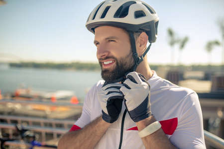 Preparing for bike ride. Concentrated young bearded man in sports gloves buttoning bicycle helmet on his head