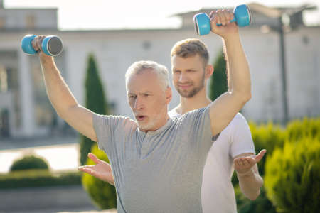Morning workout. Mature grey-haired man frowning, raising hands with dumbbells, young bearded instructor assisting him