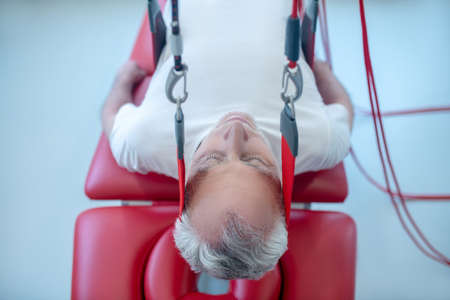 Immobility, relaxation. Elderly gray-haired lying male patient with closed eyes receiving procedure at medical center