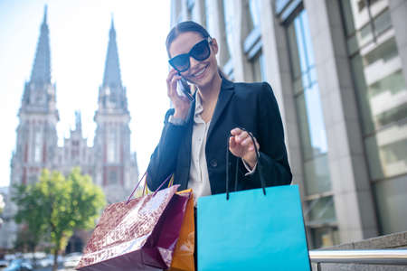 Phone call. Dark-haired woman with shopping having a phone call