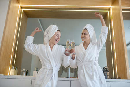 Party time. Two pretty girls in white robes spending time together and partying