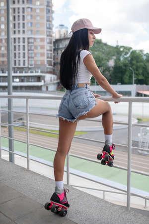 Workout. Dark-haired girl in roller-skates standing and raising one leg
