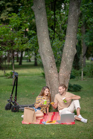 Picnic. Young couple sitting under tree and having a picnic Stockfoto